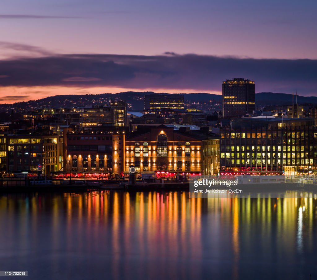 Illuminated Buildings By River Against Sky At Sunset : Stock Photo