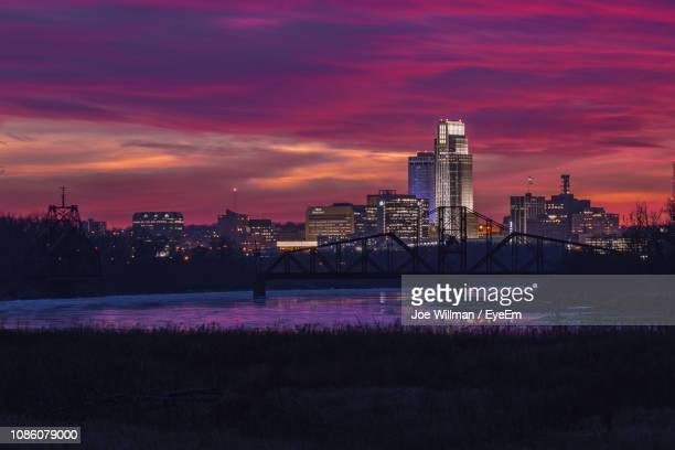illuminated buildings by river against sky during sunset - nebraska stock pictures, royalty-free photos & images