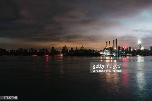 illuminated buildings by river against sky during sunset - blackout picture stock pictures, royalty-free photos & images