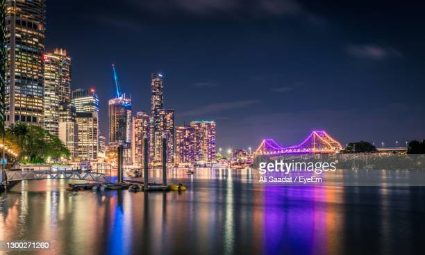 illuminated buildings by river against sky in city at night - brisbane stock pictures, royalty-free photos & images