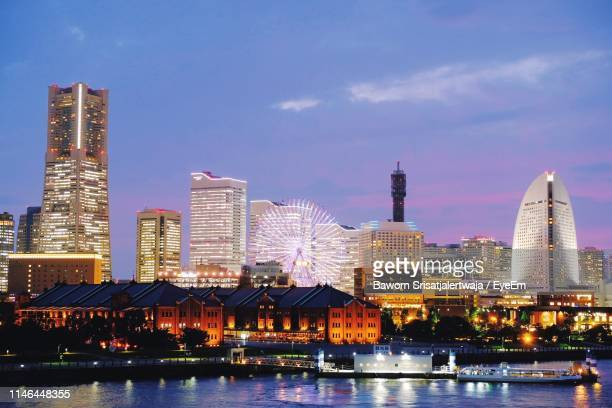illuminated buildings by river against sky in city during sunset - yokohama stock pictures, royalty-free photos & images
