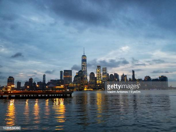 illuminated buildings by river against sky in city - antonov stock pictures, royalty-free photos & images