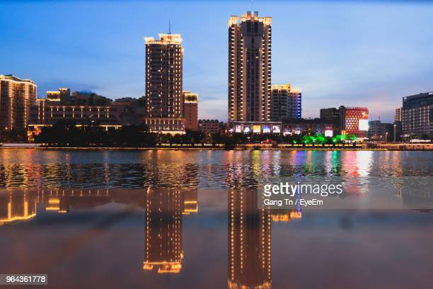 illuminated buildings by river against sky in city - sanya stock pictures, royalty-free photos & images