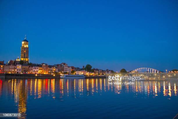 illuminated buildings by river at night - deventer stock photos and pictures
