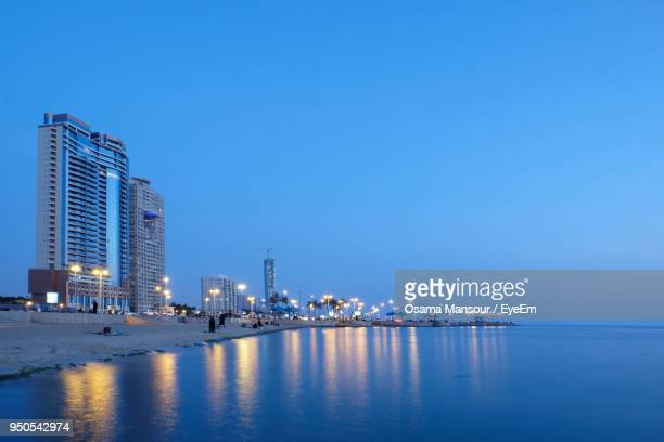 illuminated buildings by sea against clear blue sky - jiddah stock pictures, royalty-free photos & images