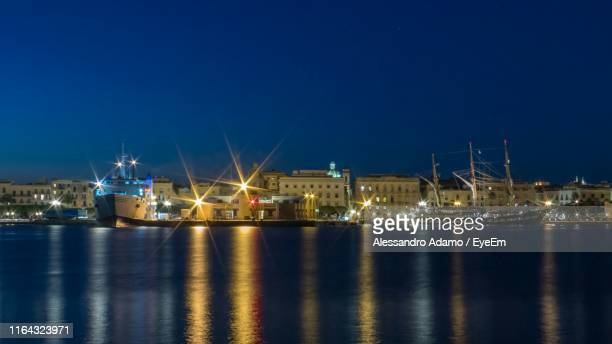 illuminated buildings by sea against clear sky at night - adamo photos et images de collection