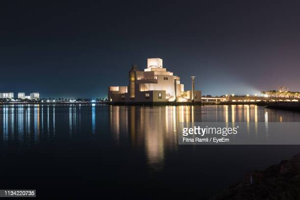 illuminated buildings by sea against sky at night - doha photos et images de collection