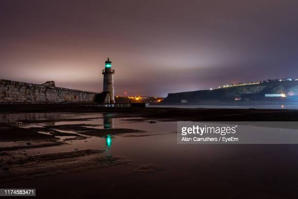illuminated buildings by sea against sky at night - whitehaven cumbria stock pictures, royalty-free photos & images