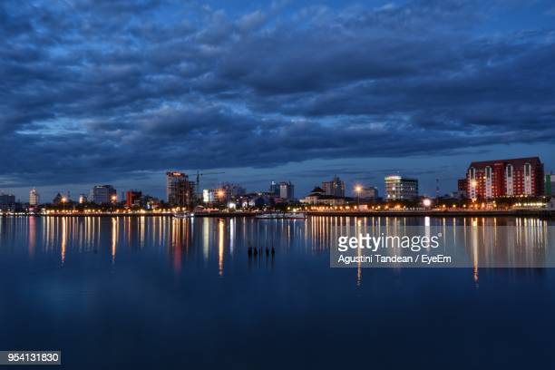 illuminated buildings by sea against sky at night - makassar stock pictures, royalty-free photos & images