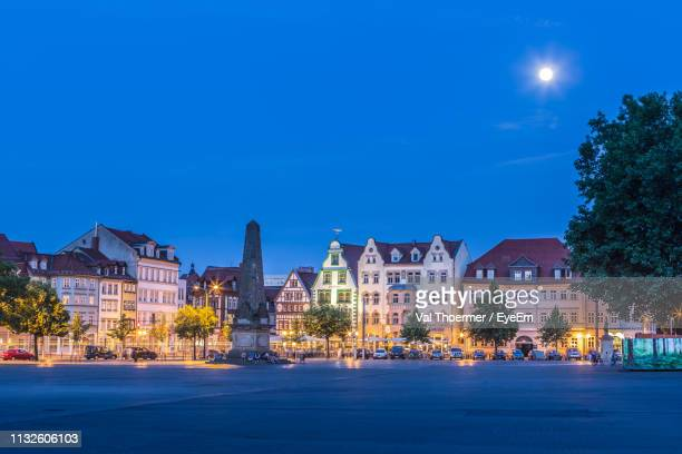 illuminated buildings by street against blue sky at night - erfurt stock pictures, royalty-free photos & images