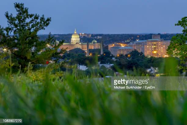 illuminated buildings in city against clear sky - harrisburg pennsylvania stock pictures, royalty-free photos & images