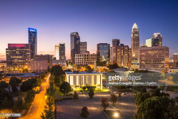 illuminated buildings in city against clear sky - charlotte north carolina stock pictures, royalty-free photos & images