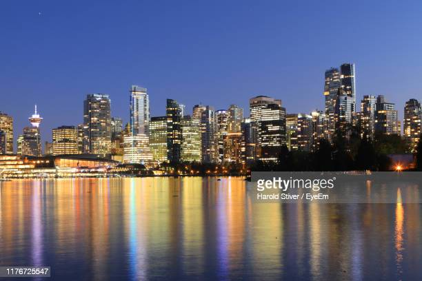 illuminated buildings in city against clear sky - vancouver skyline stock pictures, royalty-free photos & images