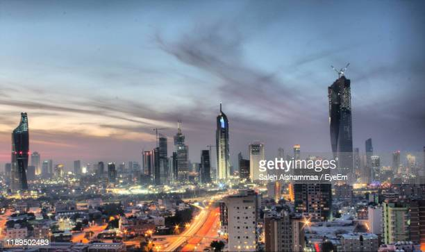 illuminated buildings in city against cloudy sky - kuwait city stock pictures, royalty-free photos & images