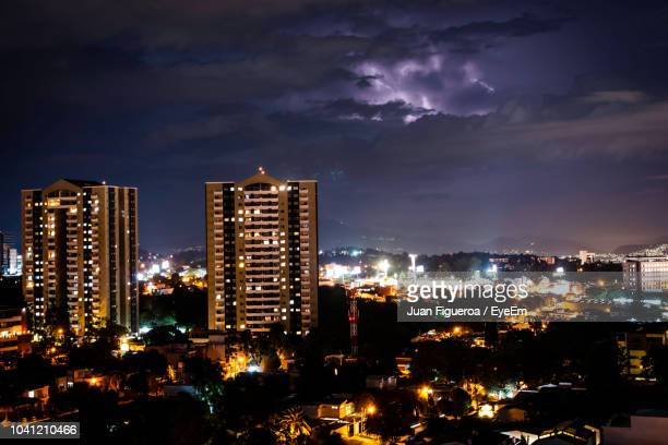 illuminated buildings in city against sky at night - guatemala city stock pictures, royalty-free photos & images
