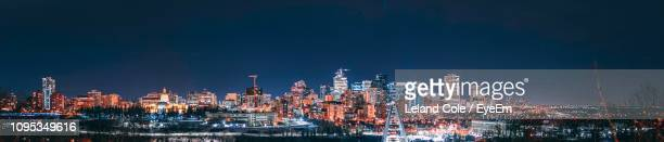 illuminated buildings in city against sky at night - edmonton stock pictures, royalty-free photos & images