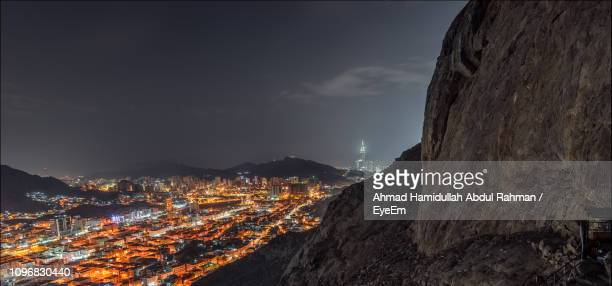 illuminated buildings in city against sky at night - mecca stock pictures, royalty-free photos & images
