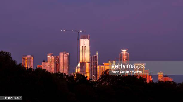 illuminated buildings in city against sky at night - florin seitan stock pictures, royalty-free photos & images