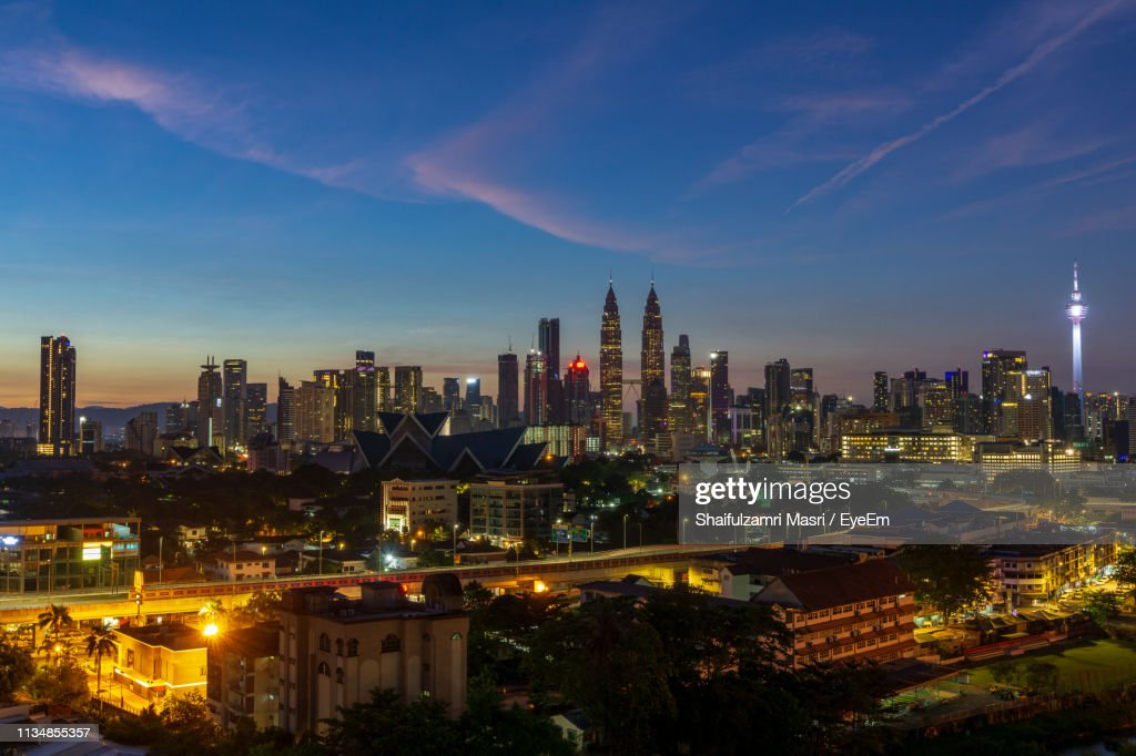 Illuminated Buildings In City Against Sky At Night : Stock Photo