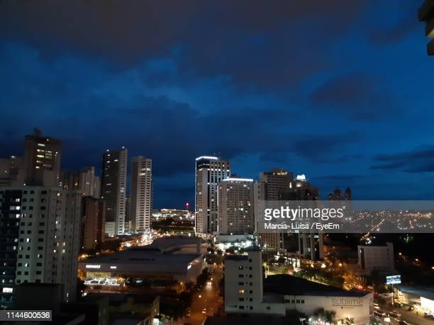 illuminated buildings in city against sky at night - goiania stock pictures, royalty-free photos & images