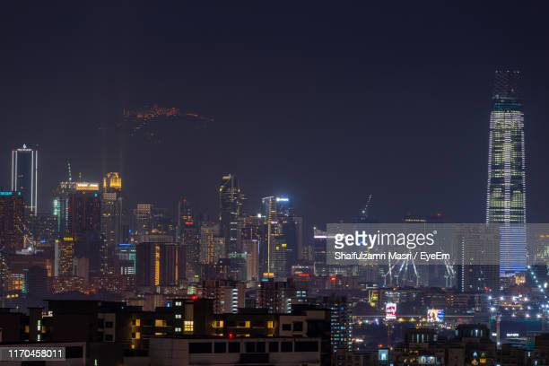 illuminated buildings in city against sky at night - shaifulzamri stock pictures, royalty-free photos & images