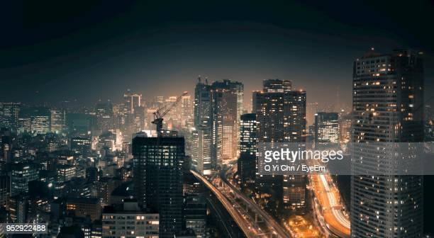 illuminated buildings in city against sky at night - kanto region stock photos and pictures