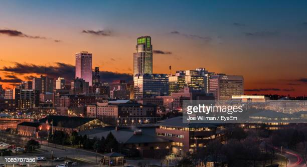 illuminated buildings in city against sky during sunset - nebraska stock photos and pictures