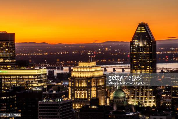 illuminated buildings in city against sky during sunset - montréal stock pictures, royalty-free photos & images