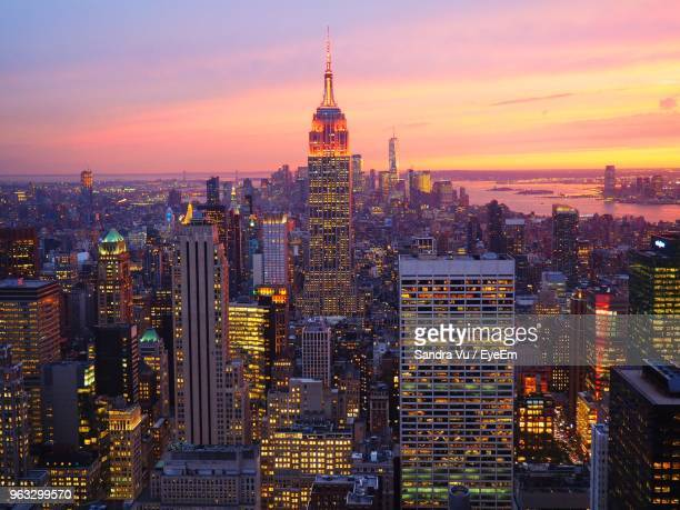 illuminated buildings in city against sky during sunset - rockefeller center stock pictures, royalty-free photos & images