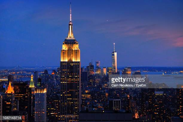 illuminated buildings in city against sky - new york city stock pictures, royalty-free photos & images