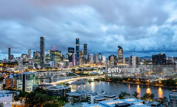 illuminated buildings in city against sky - brisbane stock pictures, royalty-free photos & images