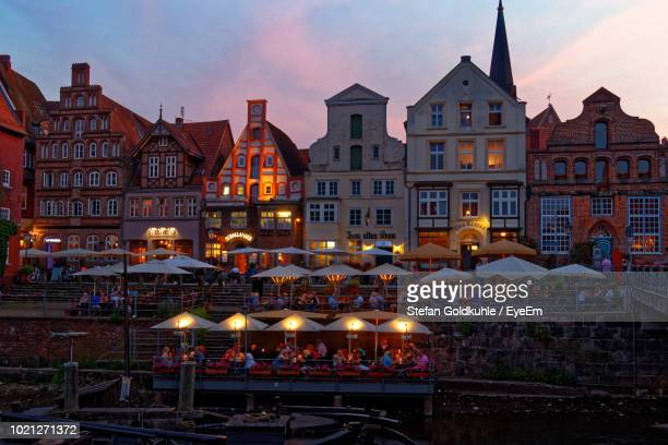 illuminated buildings in city at dusk - lüneburg stock photos and pictures