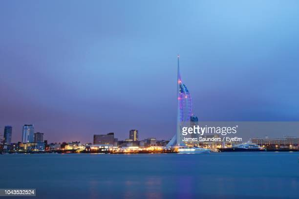 illuminated buildings in city at night - portsmouth hampshire photos et images de collection