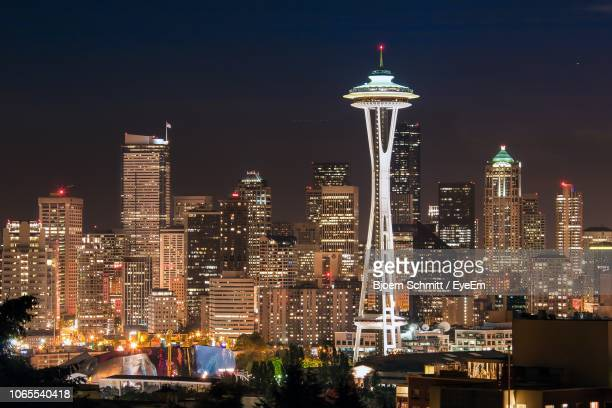 illuminated buildings in city at night - spire stock pictures, royalty-free photos & images