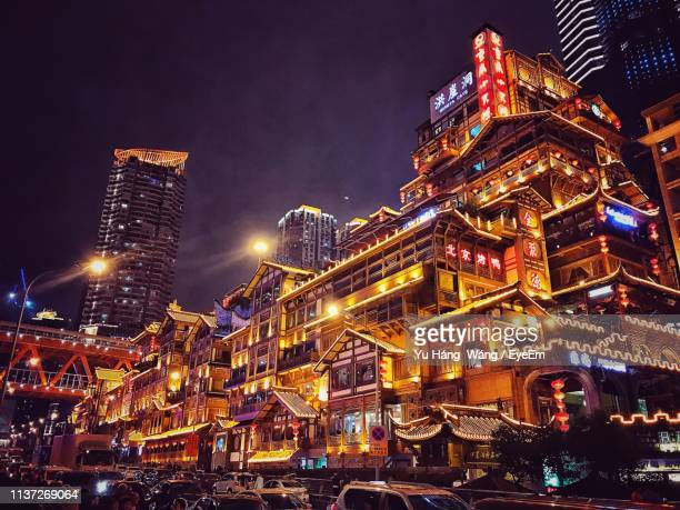 illuminated buildings in city at night - chongqing stock photos and pictures
