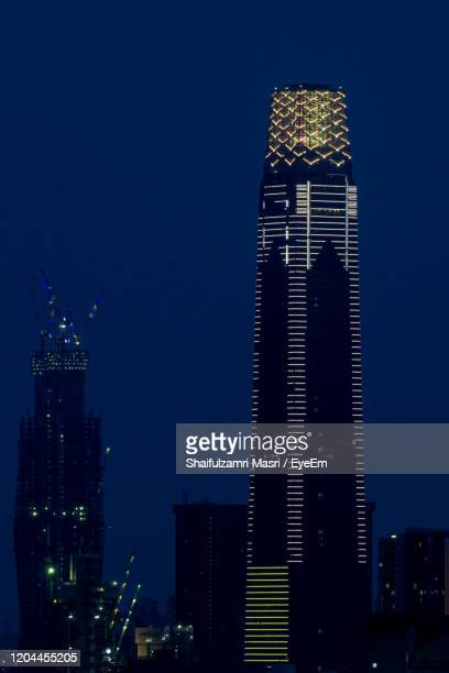 illuminated buildings in city at night - shaifulzamri stock pictures, royalty-free photos & images