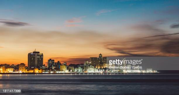 illuminated buildings in city at sunset - bortes stock pictures, royalty-free photos & images