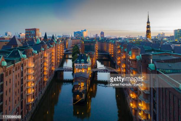 illuminated buildings in city at waterfront - hamburg germany stock pictures, royalty-free photos & images