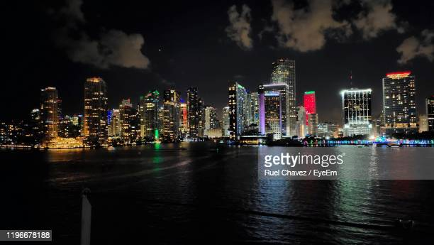 illuminated buildings in city by river against sky at night - ruel stock pictures, royalty-free photos & images