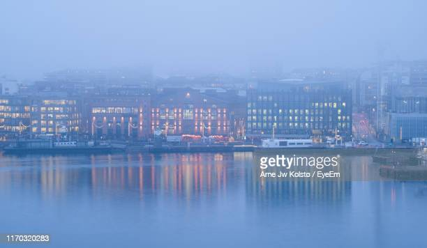 illuminated buildings in city by river at dusk during foggy weather - arne jw kolstø stock pictures, royalty-free photos & images