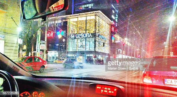 Illuminated Buildings In City Seen Through Car