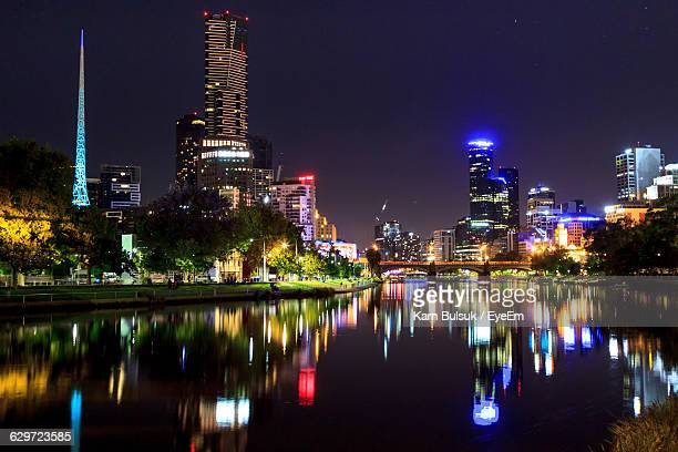 Illuminated Buildings With Reflection In Yarra River Against Sky At Night