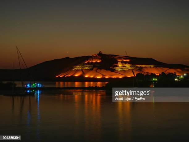 Illuminated Built Structure By Sea Against Sky At Night
