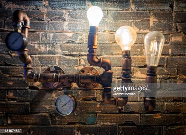 Illuminated bulbs on pipe against brick wall