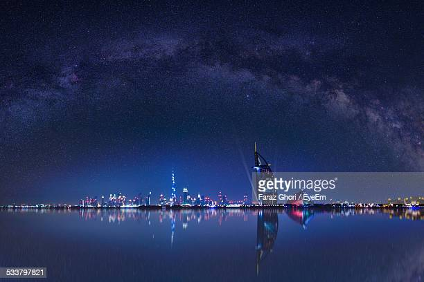 Illuminated Burj Al Arab Hotel And City By Sea At Night