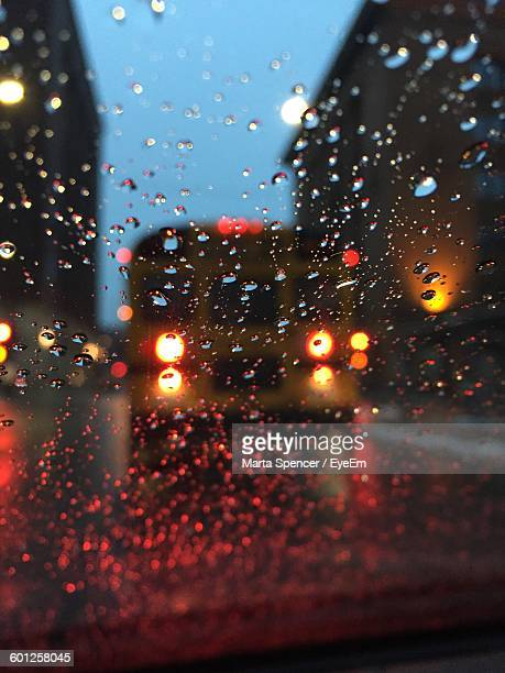 Illuminated Bus On Street Seen From Wet Car Windshield During Monsoon