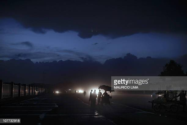 Illuminated by cars headlights Afghan men buy some food with a street vendor at nightfall as the rain approaches in the old part of Kabul on April 10...