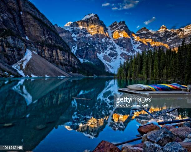 Illuminated by the morning sun, the Canadian Rockies are reflected in the still waters of Moraine Lake..