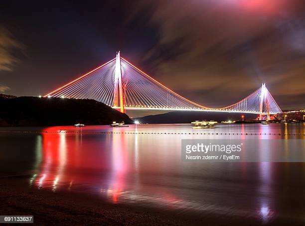 Illuminated Cable-Stayed Bridge Over River Against Sky At Night