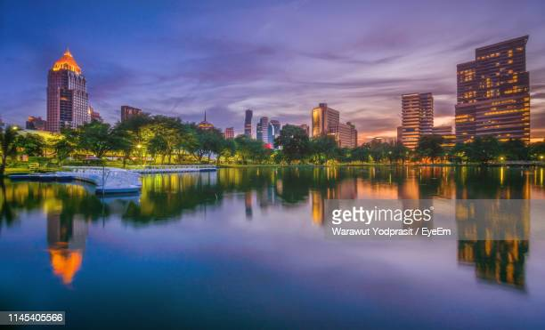 illuminated calm lake with buildings reflection against sky in city - thai mueang photos et images de collection